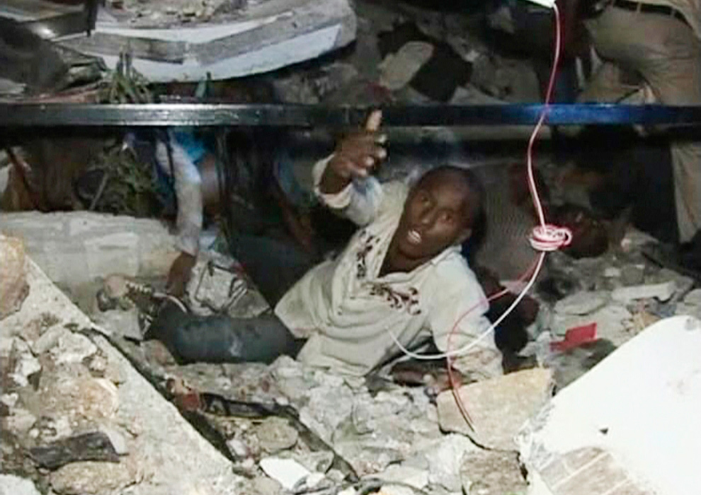 7. Мужчина зовет на помощь, застряв под обломками здания университета в Порт-о-Пренс 12 января. (REUTERS/Reuters TV)