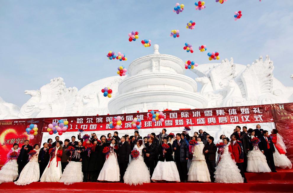 10. Пары принимают участие в групповой свадебной церемонии перед изображением Пекинского Храма Небес из снега 6 января 2010 года. Свадьба была организована правительством, и в церемонии приняли участие 28 пар, на которой присутствовали представители местных органов самоуправления. (REUTERS/Aly Song)