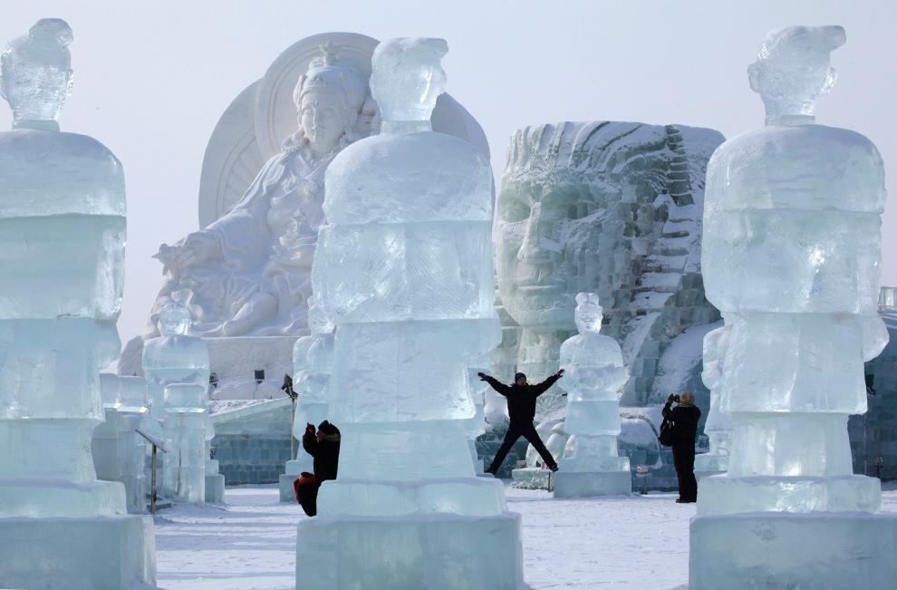 11. Посетители 26-ого Международного фестиваля снега и льда позируют рядом с гигантскими скульптурами в Харбине 5 января 2010 года. (AP Photo/Ng Han Guan)
