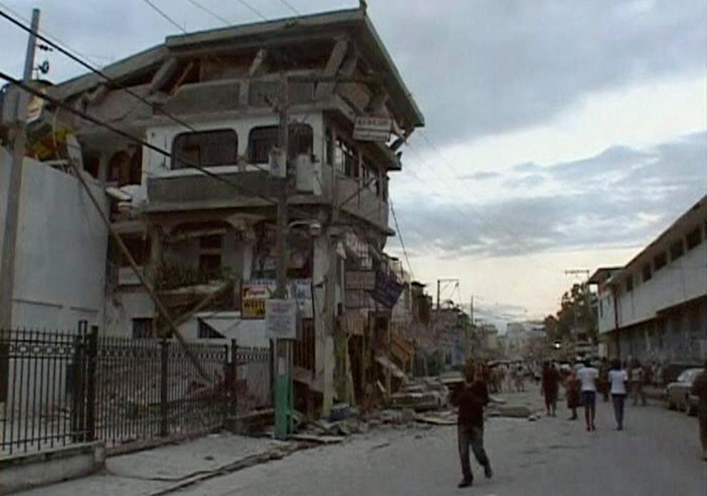 8. Люди идут по улице с разрушенными от землетрясения домами в Порт-о-Пренс 12 января. (REUTERS/Reuters TV)