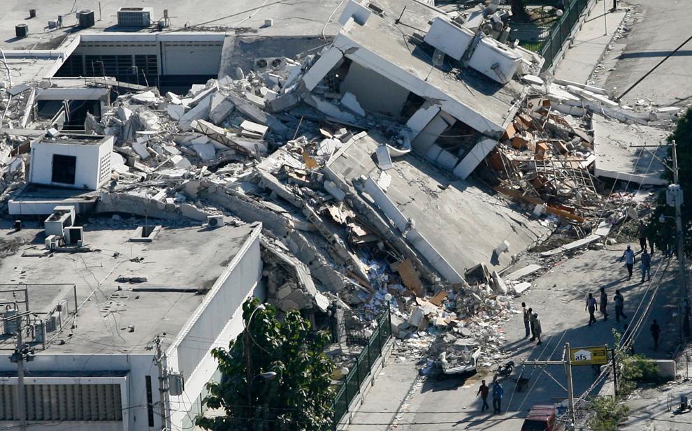 11. Гаитянцы осматривают ущерб, нанесенный землетрясением зданию, обрушившемуся на дорогу в центре Порт-о-Пренс, 17 января 2010 года. (REUTERS/Hans Deryk)