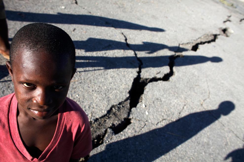 12. Дети проходят мимо трещины, образовавшейся после землетрясения на улице Порт-о-Пренс 16 января 2010 года. (REUTERS/Carlos Barria)