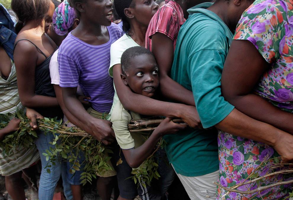12. 9-летний Сонсонн Семтембре держится за ветку дерева, стоя в очереди за провизией у передовой оперативной базы 82-ой ВДД США в Порт-о-Пренс 20 января 2010 года. (AP Photo/Jae C. Hong)