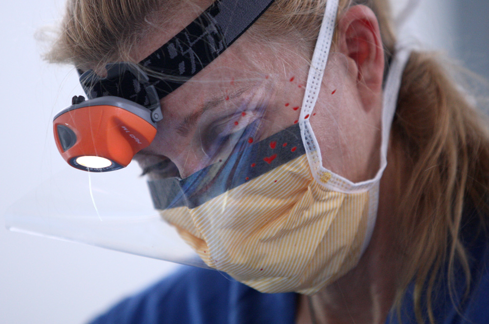 13. С пятнами крови на маске Пир Бутин – ортопедический хирург из госпиталя «Фэйрвью» в Грейт Баррингтоне, штат Массачусетс, с помощью бензопилы ампутирует женщине ногу. Снимок сделан в главной больнице Порт-о-Пренс 16 января 2010 года. (Globe staff/Bill Greene)