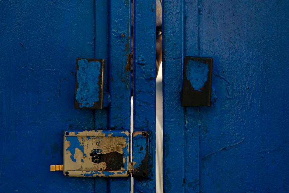 13. Человек выглядывает из-за ворот у здания Международного комитета Красного Креста в Порт-о-Пренс 16 января 2010 года. (AP Photo/Ricardo Arduengo)