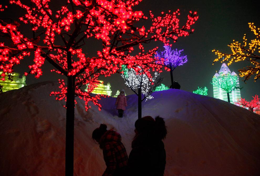 14. Девочка стоит среди ярко освещенных деревьев на Международном фестивале снега и льда в Харбине 6 января 2010 года. (AP Photo/Ng Han Guan)