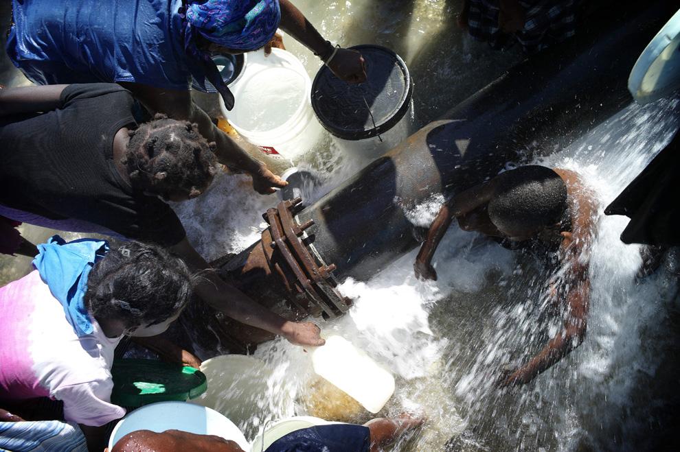 14. Люди набирают воду после прорыва трубы 16 января 2010 года в трущобах «Сити Солейл» в Порт-о-Пренс после 7балльного землетрясения 12 января. (Olivier Laban Mattei/AFP/Getty Images)