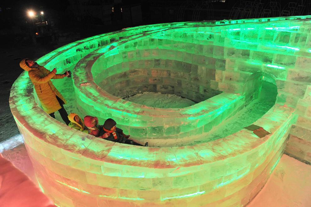 15. Посетители выставки играют в ледяной скульптуре до открытия фестиваля в Харбине 18 декабря 2009 года. (REUTERS/Sheng Li)