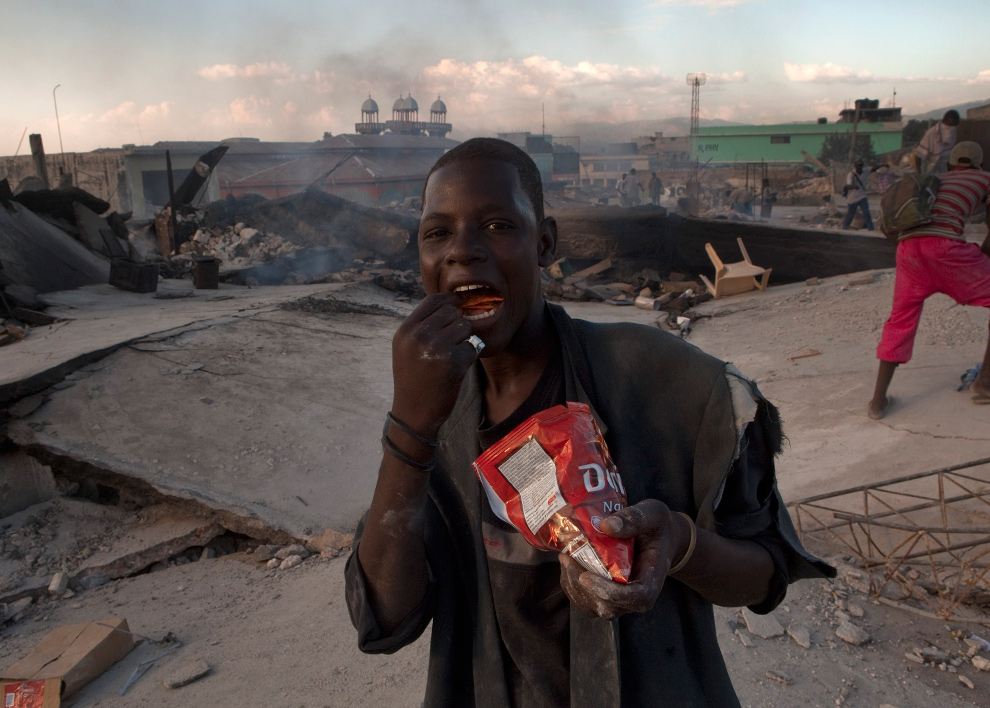 15. Мужчина есть чипсы, найденные в обломках здания в Порт-о-Пренс 20 января 2010 года. (AP Photo/Ramon Espinosa)