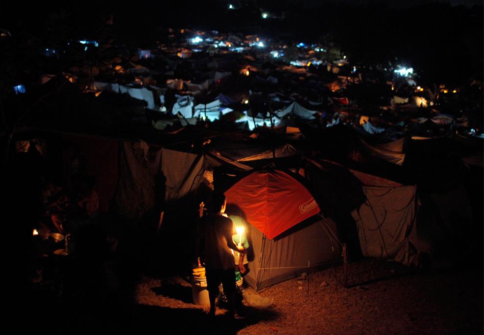 18. Мальчик держит свечу в лагере для выживших после землетрясения в Порт-о-Пренс 17 января 2010 года. (AP Photo/Jae C. Hong)