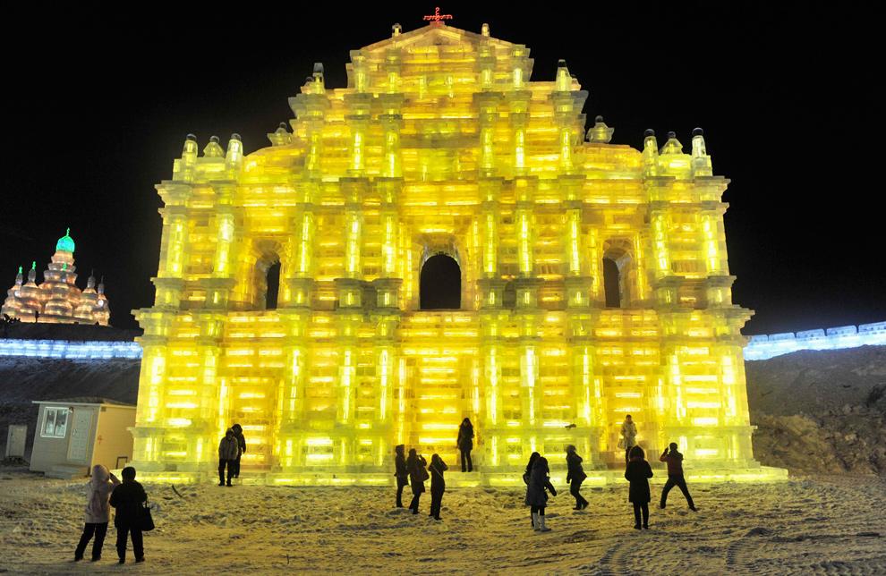 19. Люди пришли посмотреть на ярко освещенную изнутри ледяную скульптуру в Харбине 24 декабря 2009 года. (REUTERS/Sheng Li)