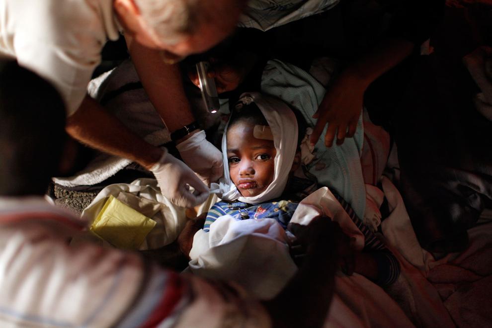 12. Медики помогают раненому ребенку после землетрясения в Порт-о-Пренс 13 января. (REUTERS/Eduardo Munoz)