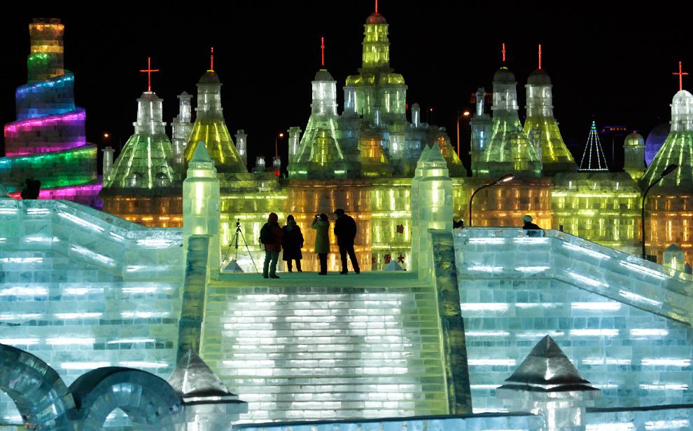 20. Посетители гуляют между зданиями изо льда на Международном фестивале снега и льда в Харбине 5 января 2010 года. (AP Photo/Ng Han Guan)