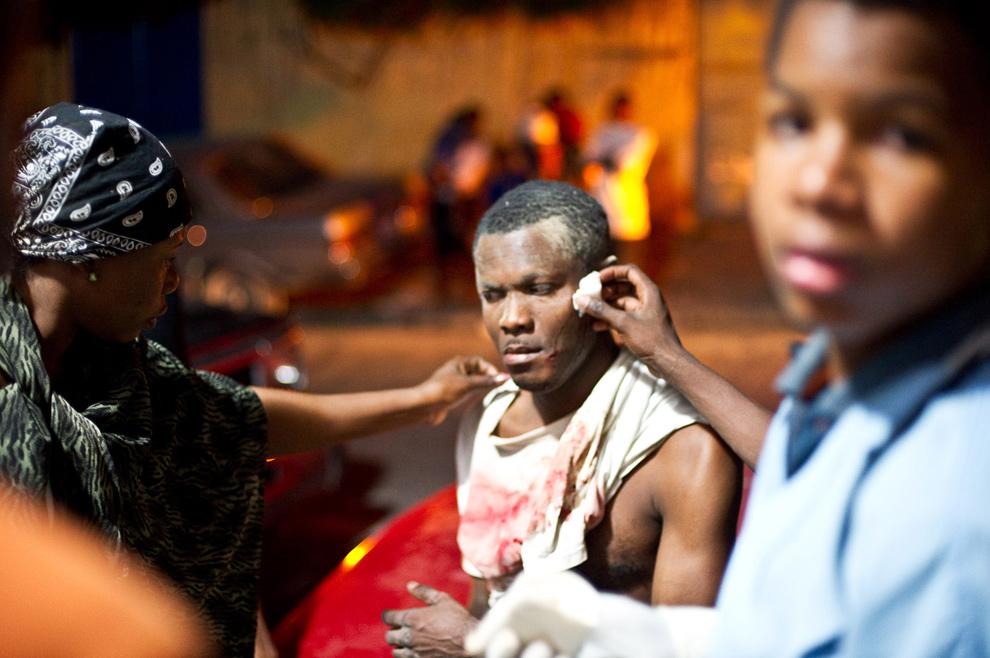 13. Люди приходят на помощь раненому человеку после землетрясения в Порт-о-Пренс 12 января. (Frederic Dupoux/Getty Images)