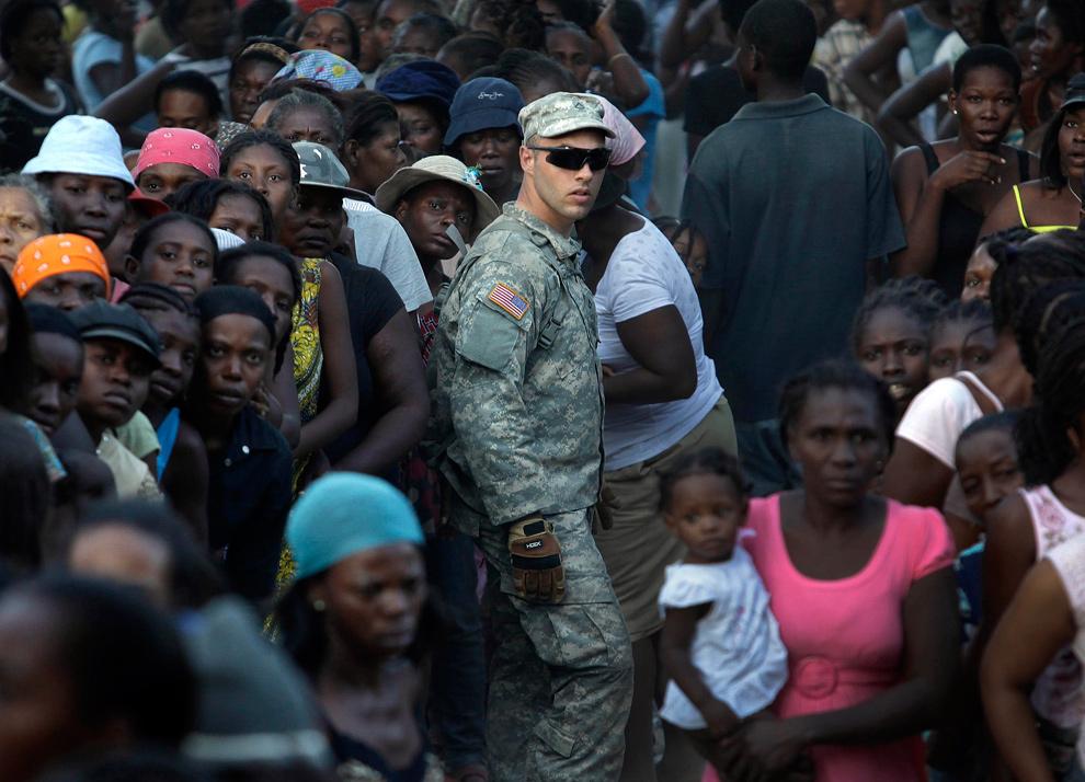 20. Рядовой первого класса Томас из 82-ой ВДД США помогает поддерживать порядок в толпе из 2000 человек во время раздачи воды в лагере, разбитом на гольф-поле в Порт-о-Пренс 20 января 2010 года. (AP Photo/Julie Jacobson)