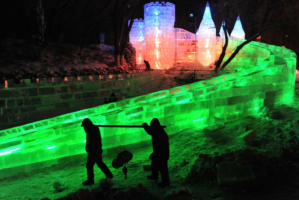 21. Рабочие проходят мимо ледяной скульптуры на фестивале в Харбине 18 декабря 2009 года. (REUTERS/Sheng Li)