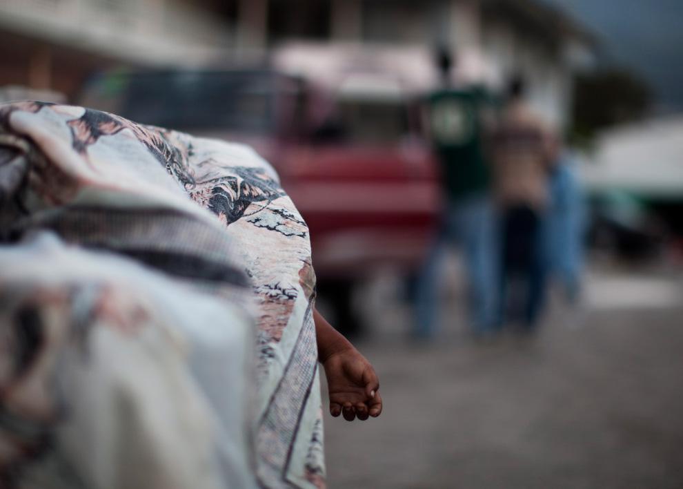 21. Тело маленького мальчика лежит на столе у морга при главной больнице 16 января 2010 года в Порт-о-Пренс. (Uriel Sinai/Getty Images)