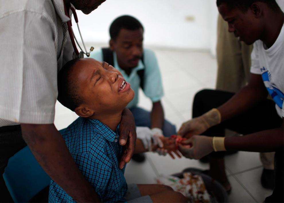 21. Мальчик скривился от боли во время операции на руке в полевом госпитале в Порт-о-Пренс 17 января 2010 года. (REUTERS/Carlos Barria)