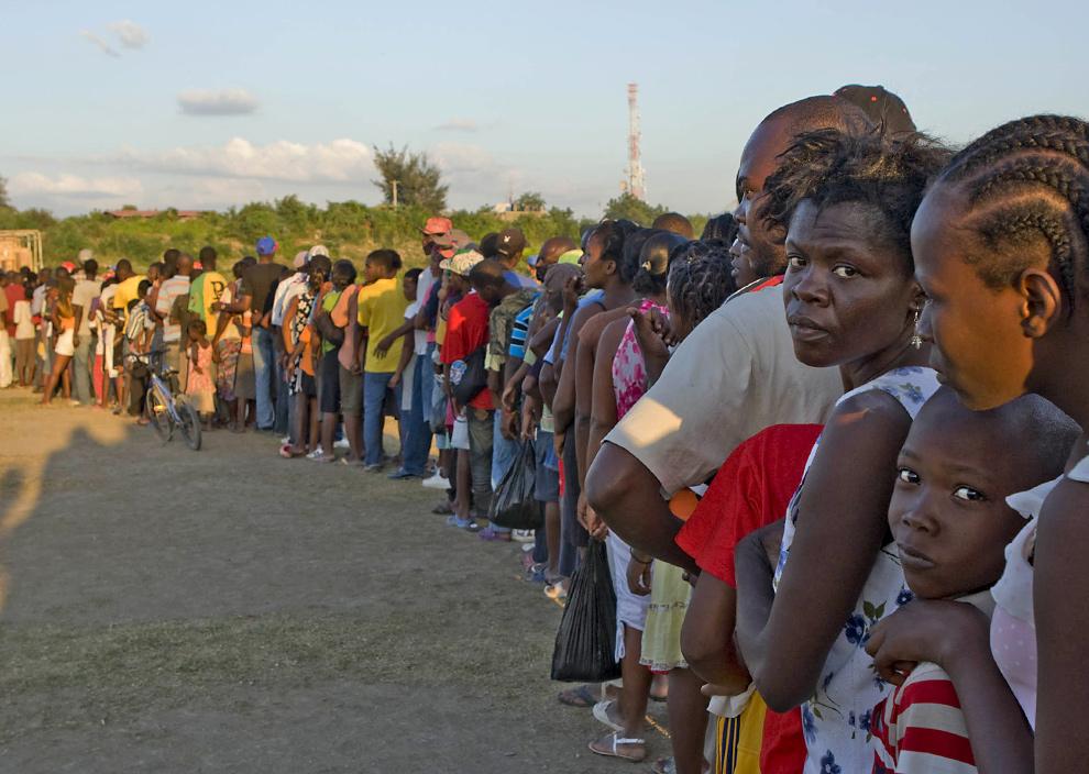 22. Два человека оглянулись, стоя в очереди за продуктами, которые распределяет ООН, в Порт-о-Пренс 18 января 2010 года. (LOGAN ABASSI/AFP/Getty Images)
