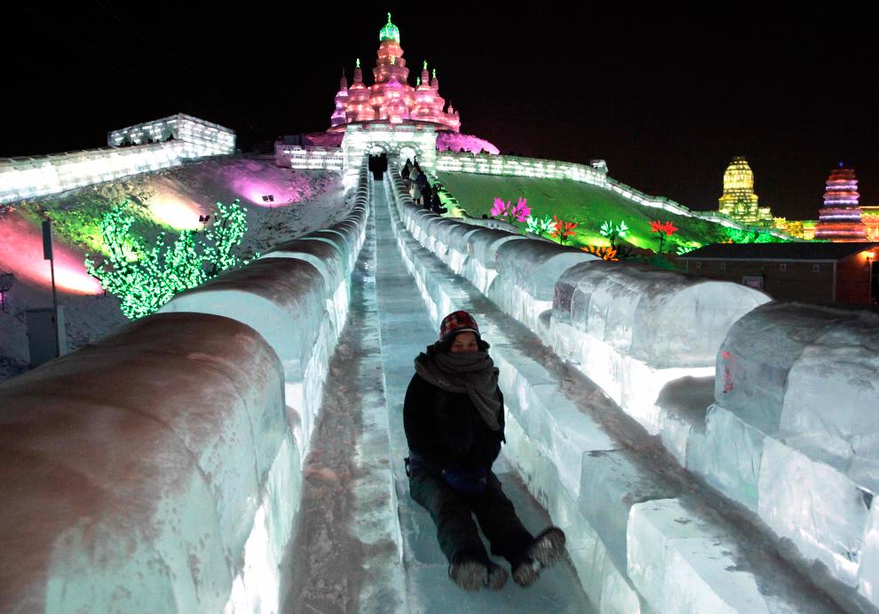 23. Женщина едет вниз с ледяной горки на фестивале в северо-восточной провинции Китая Хэйлунцзян 5 января 2010 года. (AP Photo/Ng Han Guan)
