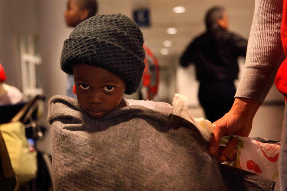 23. Ребенок, эвакуированный из Порт-о-Пренс ждет посадки на автобус в аэропорту О'Хэйр 20 января 2010 года в Чикаго. Около 70 американцев гаитянского происхождения прибыли в аэропорт вечером на самолете «United Airlines», который возвращался с Гаити, куда он отвозил гуманитарную помощь. (Scott Olson/Getty Images)