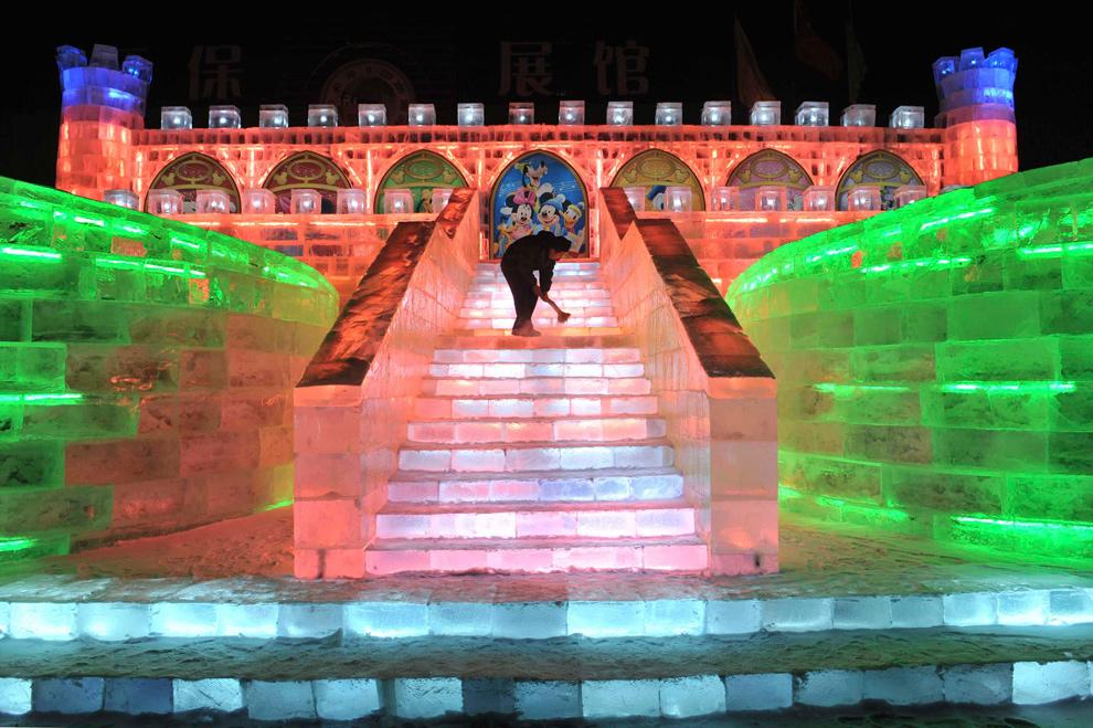 25. Рабочий чистит ледяную скульптуру в стиле Диснея перед открытием фестиваля снега и льда в Харбине 18 декабря 2009 года. (REUTERS/Sheng Li)