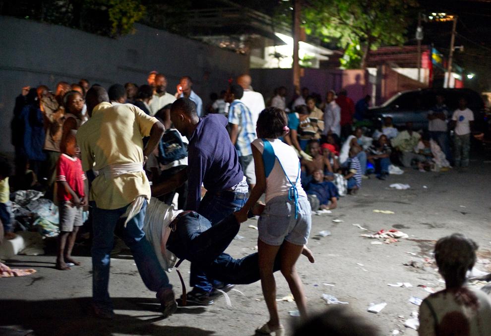 18. Оказавшиеся без дома люди выносят раненого человека из больницы, когда начался второй толчок 13 января в Порт-о-Пренс. (Frederic Dupoux/Getty Images)