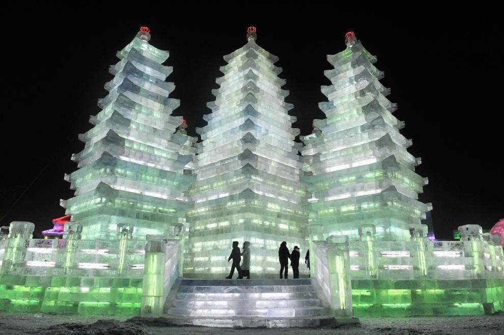 26. Люди пришли посмотреть на высокие ледяные пагоды в Харбине, провинция Хэйлунцзян, 24 декабря 2009 года. (REUTERS/Sheng Li)