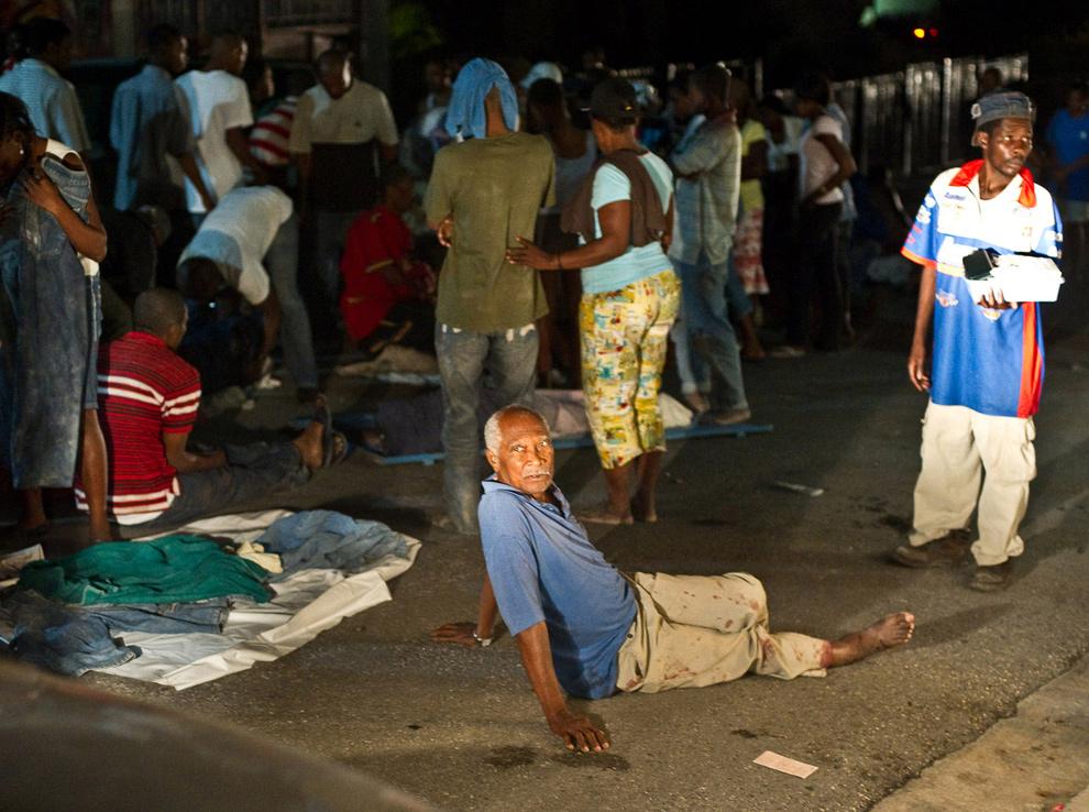 19. Мужчина с двумя поломанными ногами сидит на улице среди других раненых людей после землетрясения 13 января в Порт-о-Пренс. (Frederic Dupoux/Getty Images)