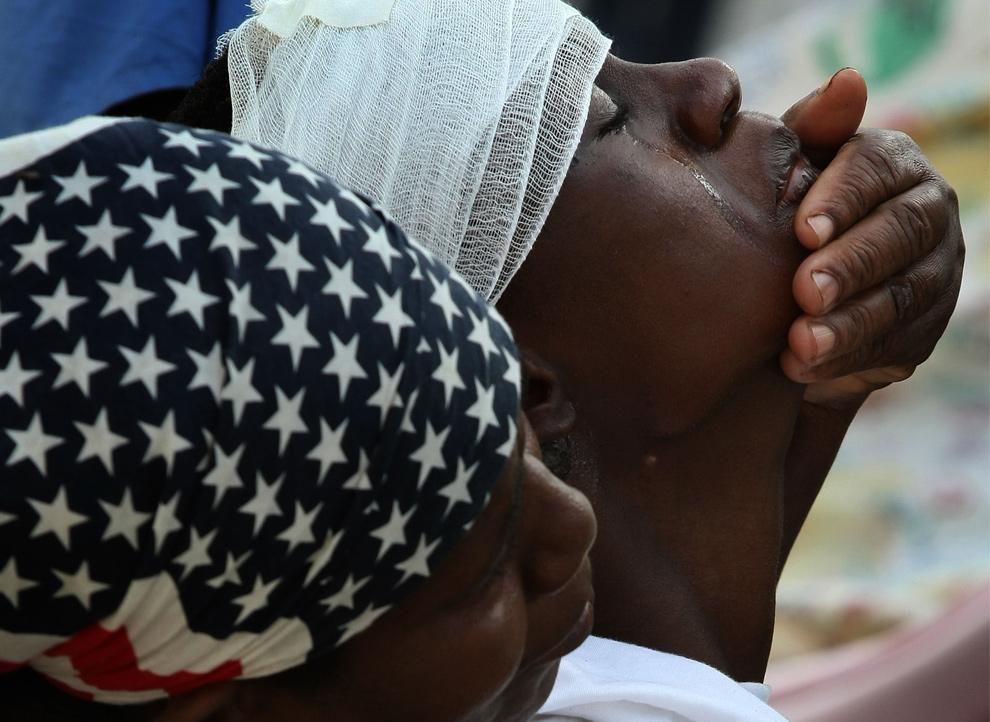 26. Мать успокаивает плачущего от боли молодого гаитянина, пока ему делают операцию на руке в медицинском центре 20 января 2010 года в Порт-о-Пренс. Немецкие и кубинские врачи лечат пациентов прямо на улице, опасаясь обвала зданий. (Win McNamee/Getty Images)