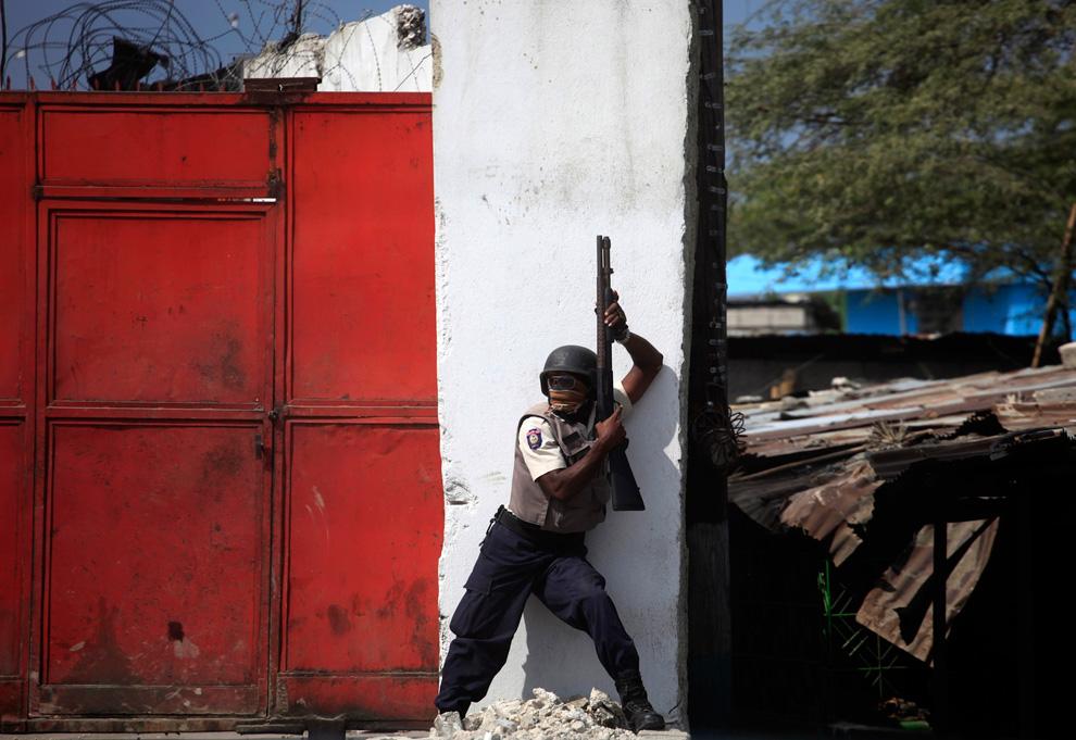 27. Офицер национальной гаитянской полиции занял позицию во время столкновения с мародерами в центре Порт-о-Пренс 17 января 2010 года. (REUTERS/Carlos Barria)