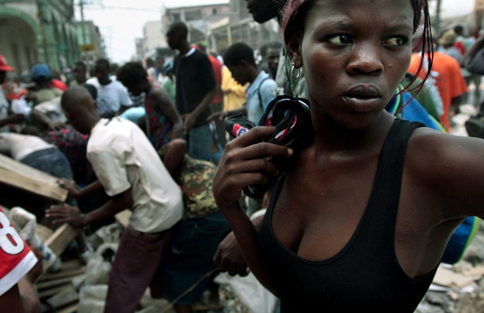 27. Гаитянка стоит на «шухере», пока мародеры прочесывают коробки, вытащенные из-под обломков зданий в деловом центре Порт-о-Пренс 19 января 2010 года. (Chris Hondros/Getty Images)
