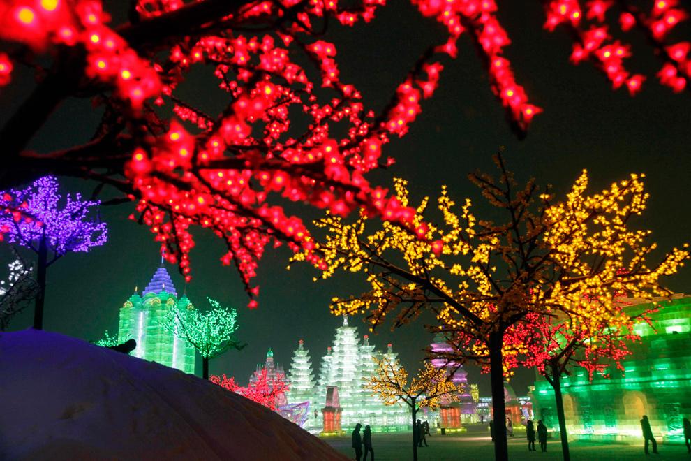 28. Освещенные яркими разноцветными гирляндами деревья и скульптуры в парке Харбина 6 января 2010 года. (AP Photo/Ng Han Guan)