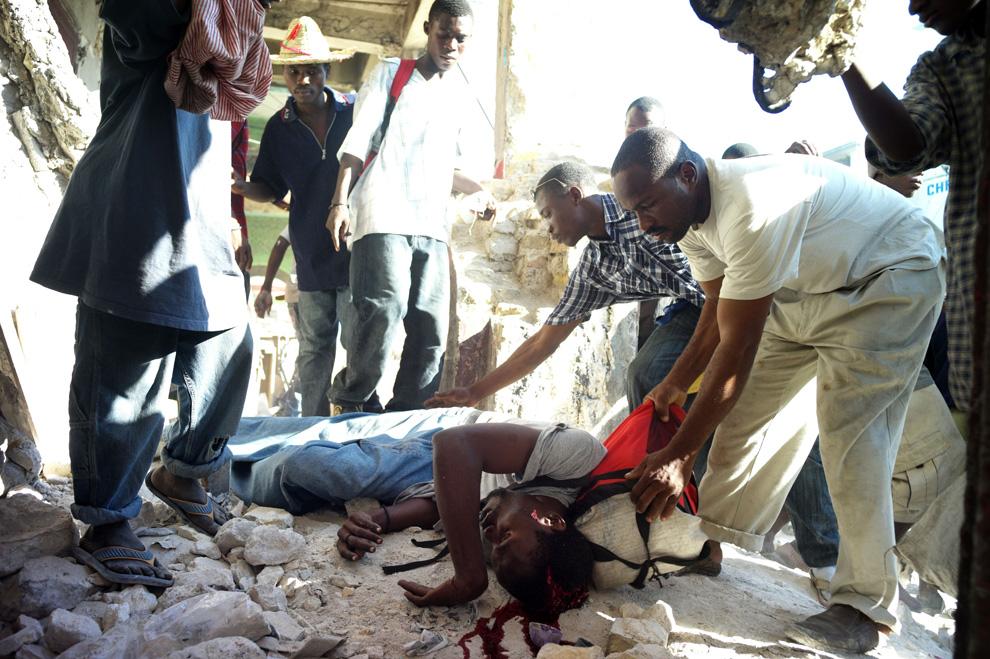 28. Мародеры забирают сумку другого мародера, застреленного полицией, 17 января 2010 года на рынке Hypolite в Порт-о-Пренс. (Olivier Laban Mattei/AFP/Getty Images)