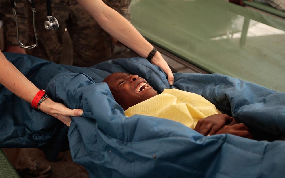 28. Серьезно раненный гаитянин кричит от боли во время перевозки на каталке на борт плавучего госпиталя «USNS Comfort» 21 января 2010 года в столице Гаити Порт-о-Пренс. (Chris Hondros/Getty Images)