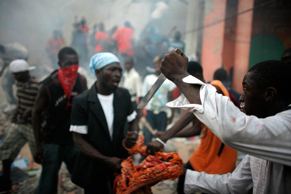 29. Мародеры дерутся у разрушенного магазина в центре Порт-о-Пренс 17 января 2010 года. (REUTERS/Eduardo Munoz)