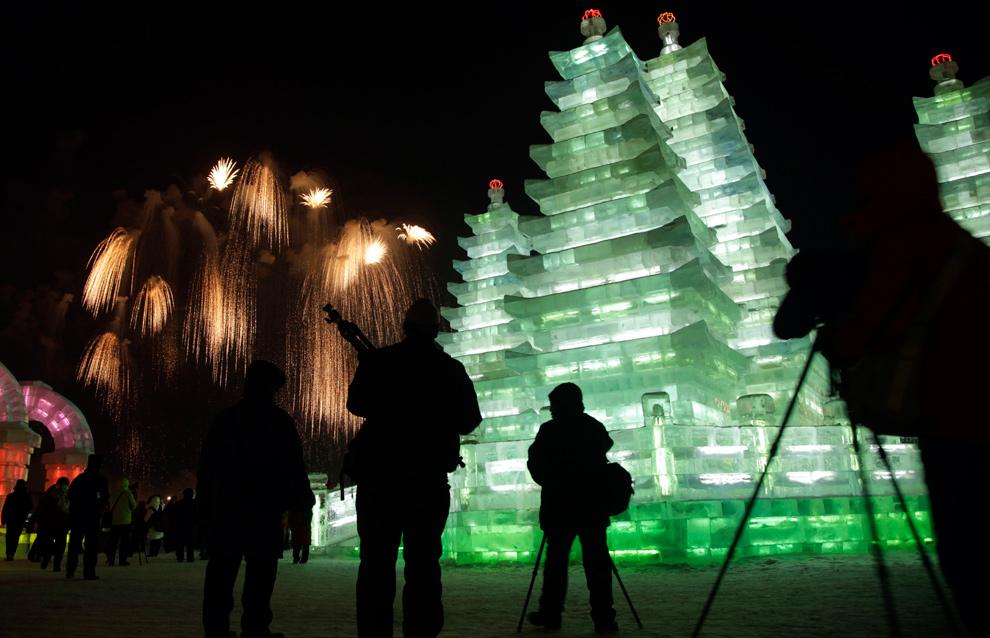 30. Посетители фестиваля снега и льда смотрят салют в северо-восточной провинции Хэйлунцзян, Китай, 5 января 2010 года. (AP Photo/Ng Han Guan)