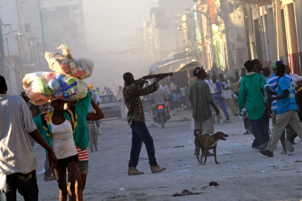 30. Мужчина нацеливает оружие на толпу в центре Порт-о-Пренса 15 января 2010 года. Мужчина сделал несколько предупредительных выстрелов в воздух, чтобы разогнать мародеров, напавших на его магазин. (REUTERS/Kena Betancur )