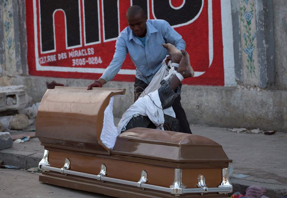 31. Мужчина вытаскивает тело жертвы землетрясения из гроба, чтобы украсть гроб. Снимок сделан на кладбище в Порт-о-Пренс 15 января 2010 года. (AP Photo/Ramon Espinosa)