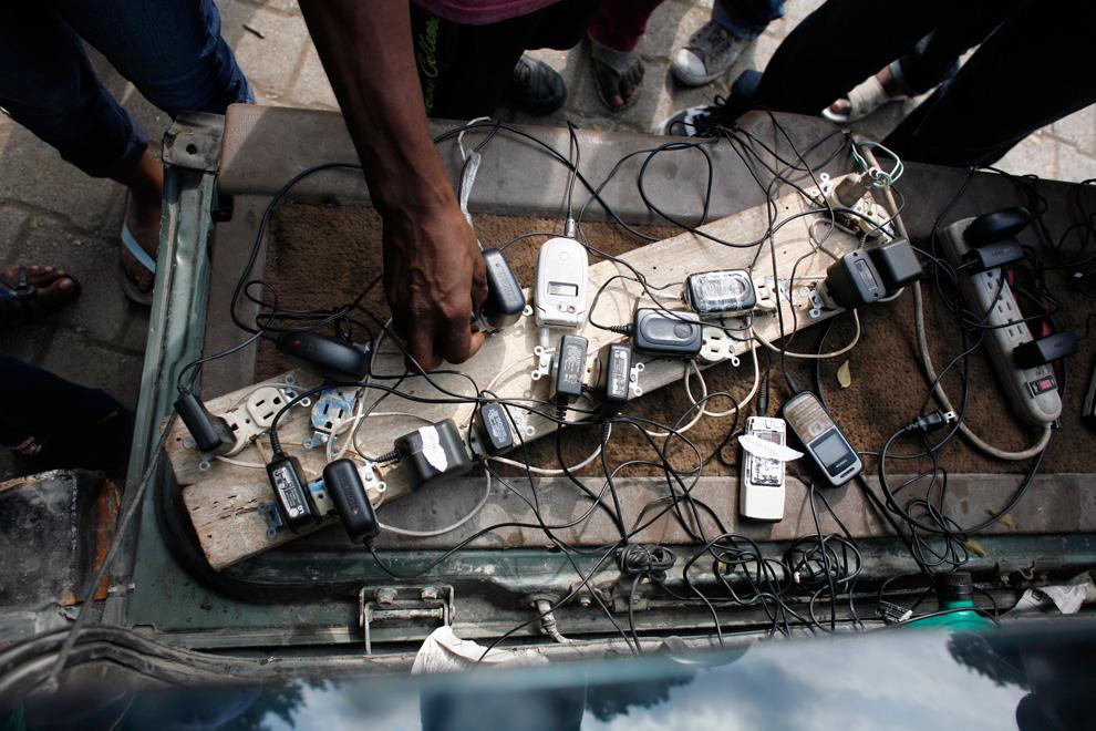 33. Мужчина сдает в аренду зарядки для мобильных телефонов на час в центре Порт-о-Пренс 17 января 2010 года. (REUTERS/Eduardo Munoz)