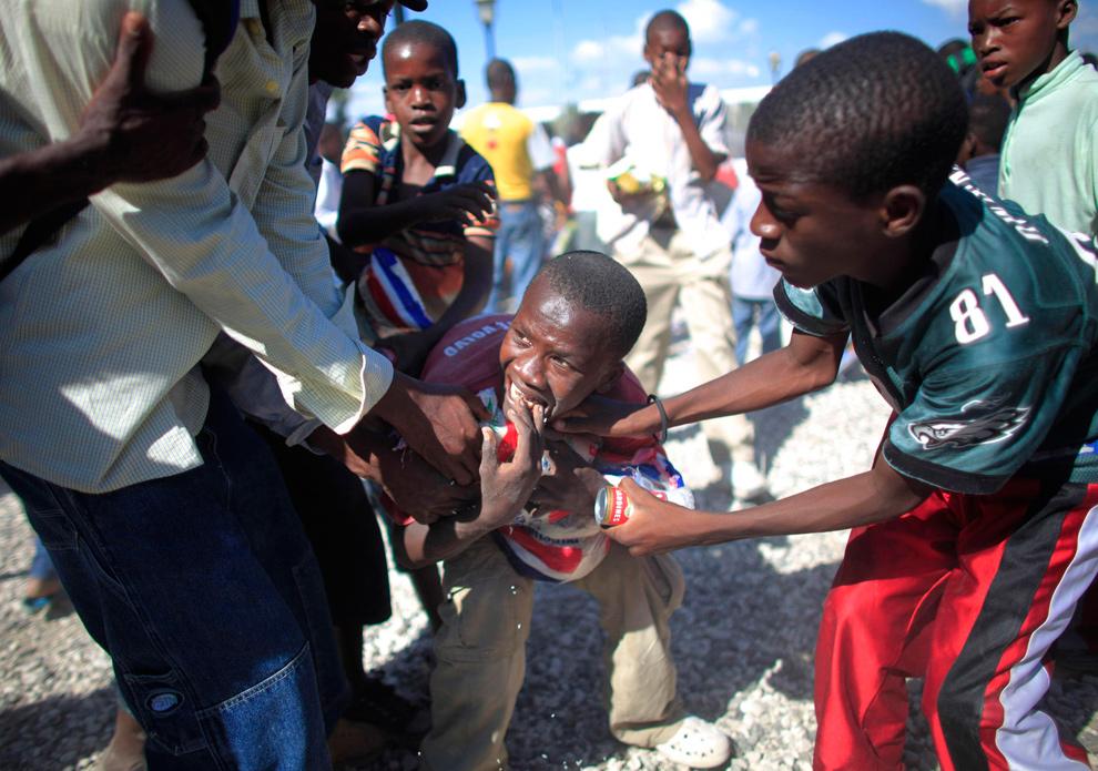 34. Мальчики дерутся за еду во время ее раздачи перед аэропортом в Порт-о-Пренс 20 января 2010 года. (REUTERS/Carlos Barria)