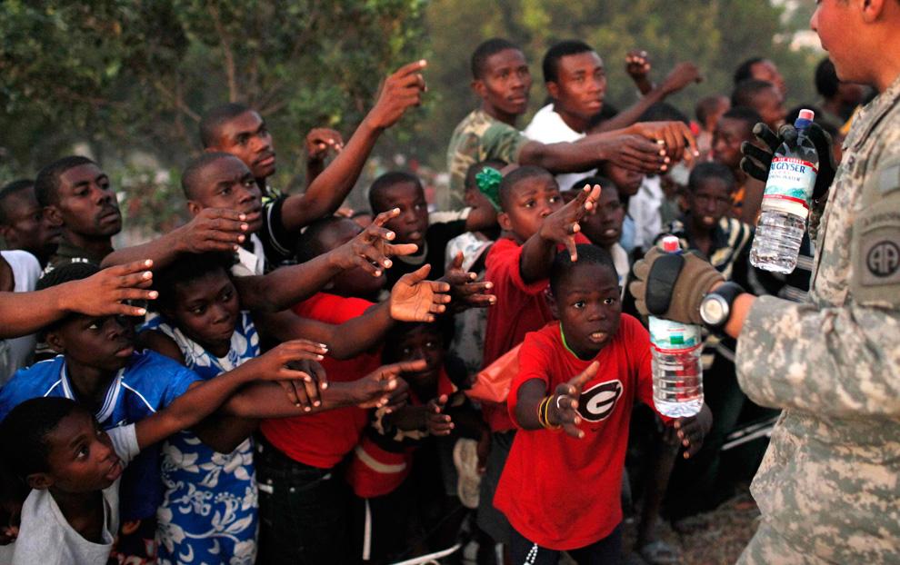 37. Выжившие в землетрясении тянут руки к воде в бутылках, раздаваемой солдатами 82- ВДД в Порт-о-Пренс 17 января 2010 года. Солтады раздали более 9000 бутылок воды и 2000 продуктов только за воскресенье. (AP Photo/Jae C. Hong)