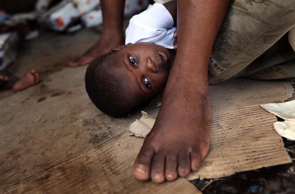 37. Сирота лежит на земле в приюте «Maison des Enfants De Dieu» 20 января 2010 года в Порт-о-Пренс. Многие страны, включая США, оказывают помощь пострадавшим от мощного землетрясения. (Joe Raedle/Getty Images)