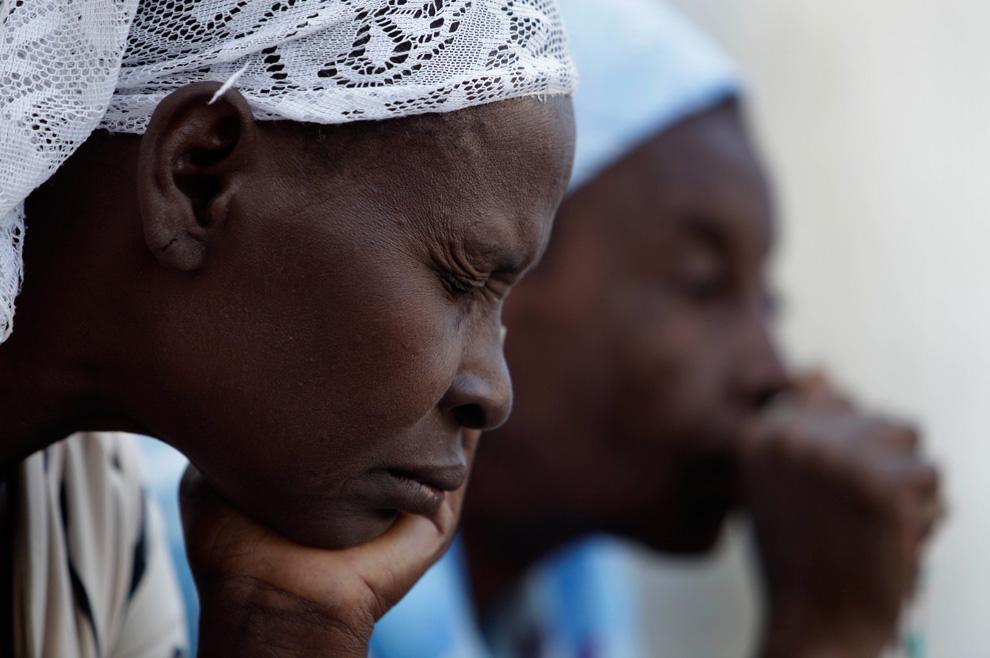 38. Женщины молятся во время службы у главного собора города Порт-о-Пренс 17 января 2010 года. Около сотни человек пришли на службу, проводимую у полностью разрушенного землетрясением собора. (AP Photo/Gregory Bull)