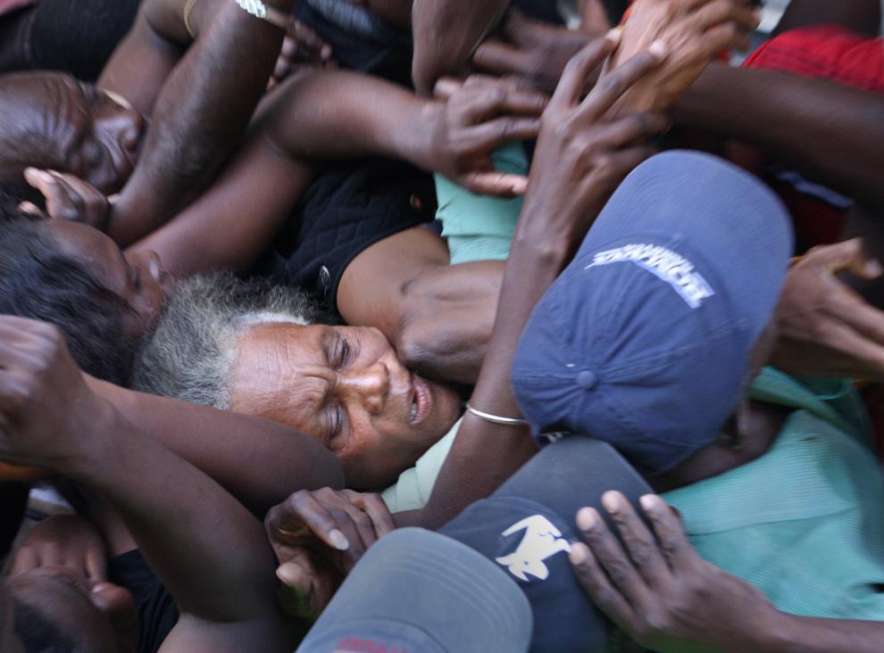38. Гаитянка попала в давку, пытаясь получить воду и еду во время их раздачи в Петьон Вилле, 21 января 2010 года. (Globe staff/Bill Greene)