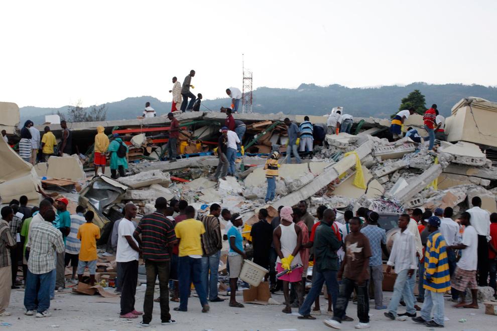29. Местные жители в поисках выживших среди обломков рухнувших зданий в Порт-о-Пренс 13 января 2010 года. (REUTERS/Eduardo Munoz)