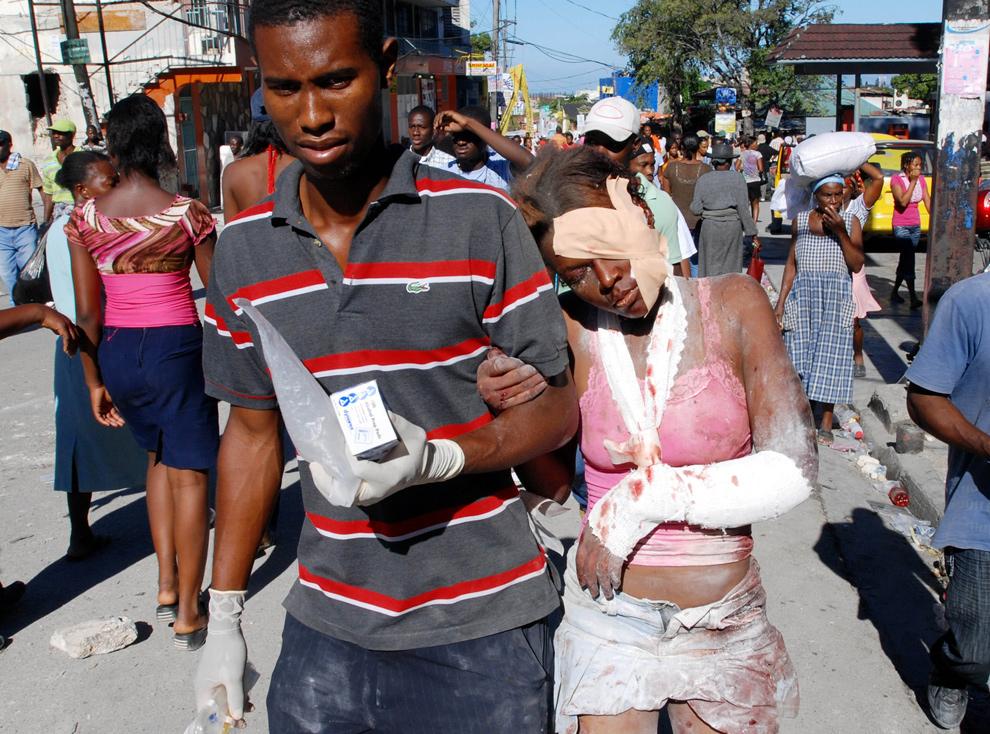 30. Раненую девушку ведут по одной из улиц гаитянской столицы. (THONY BELIZAIRE/AFP/Getty Images)