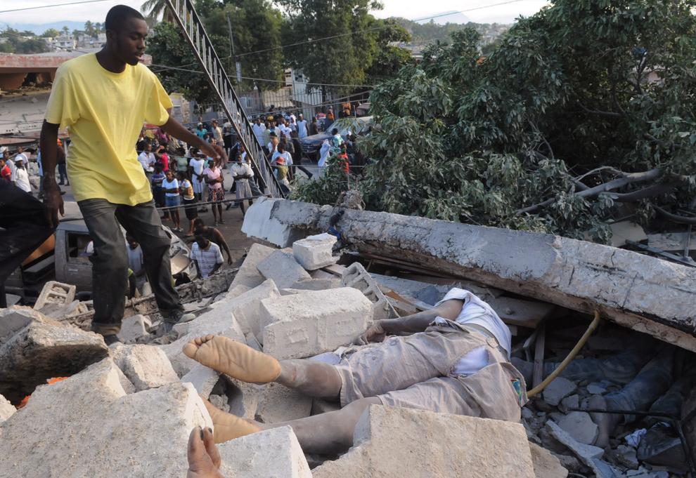 31. Молодой человек подходит к трупам, лежащим в обломках здания у дороги Делмас в гаитянской столице. (AP Photo/Jorge Cruz)