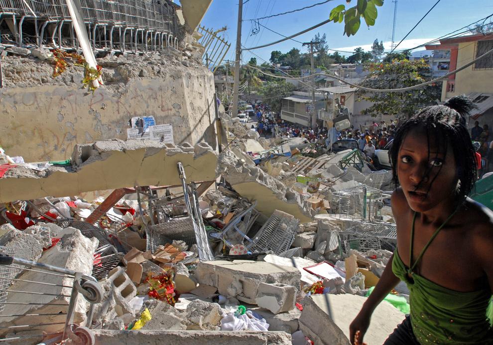 32. Через день после землетрясения девушка пробирается через обломки супермаркета. (THONY BELIZAIRE/AFP/Getty Images)