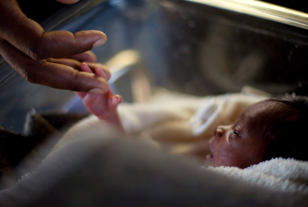 46. Мужчина прикасается к младенцу, рожденному три дня назад в израильском госпитале Порт-о-Пренс 20 января 2010 года. (REUTERS/Carlos Garcia Rawlins)